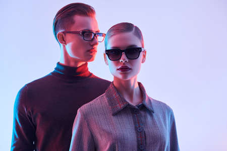 Fashion studio shot. Handsome young man and beautiful young woman posing together in stylish glasses. Optics style.