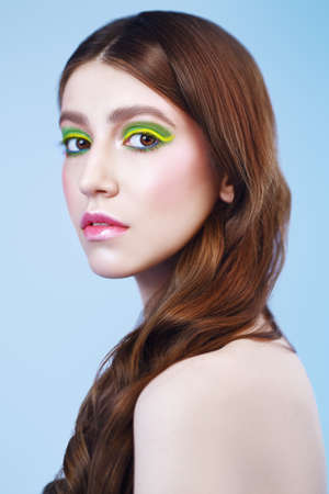 Make-up and cosmetics. Portrait of a beautiful girl with vivid colorful make-up on a blue background. Фото со стока