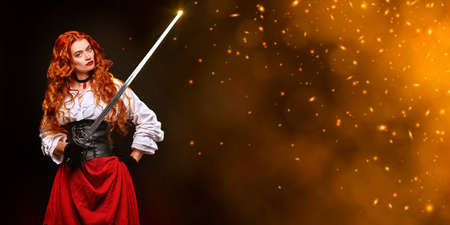 Beautiful courageous woman with long foxy hair posing with a battle epee (rapier) on a black background with fire sparks. Historical reconstruction of the 16-17th centuries. Copy space.
