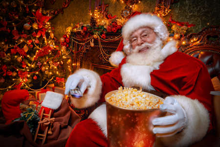 Jolly Santa Claus is sitting in a comfortable armchair at home with popcorn and soda and watching a movie. Festive New Year atmosphere and interior. Entertainment and cinema concept.