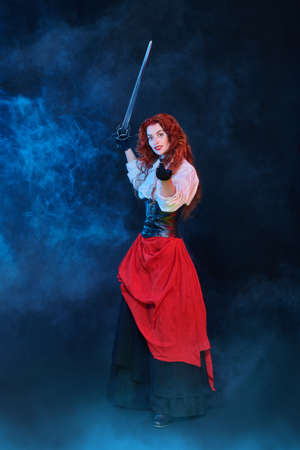 Full length portrait of a beautiful red-haired woman with a battle epee (rapier). Historical reconstruction of the 16-17th centuries. The heroine of an adventure novel.
