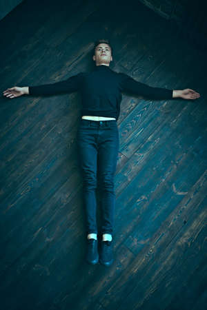 Handsome young man in black clothes lies on a black wooden floor, arms spread out to the sides. Religious concept.