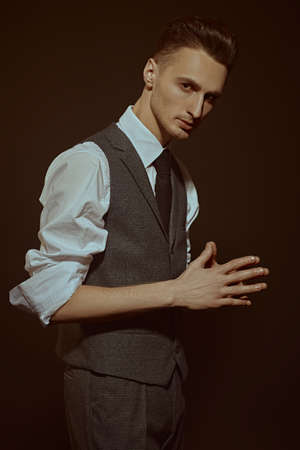 Portrait of a handsome man in elegant classic suit and a tie on a dark brown background. Business style. Men's fashion.