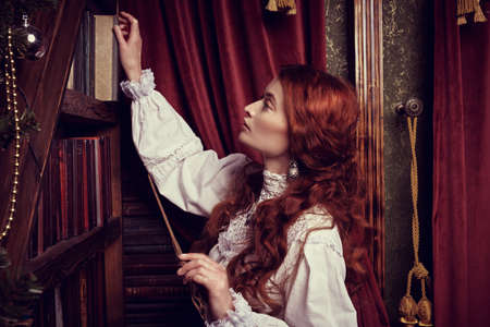 Christmas magic. Beautiful red-haired woman enchantress stands in the home library with a magic wand in her hand. Beautiful fairy christmas decoration.