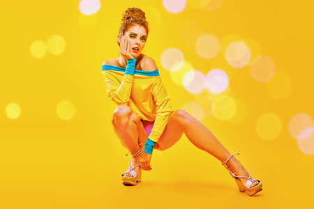Colorful life. Full length portrait of a stunning fashionable girl with colorful makeup posing on a bright yellow background in vivid clothes.