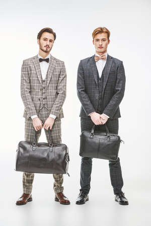 Men's fashion and accessories. Full length portrait of two elegant young men in classic three-piece suits holding leather bags on a white background.