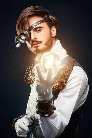 Portrait of a handsome steampunk man looking at the crystal energy ball through a monocular. Dark blue background.