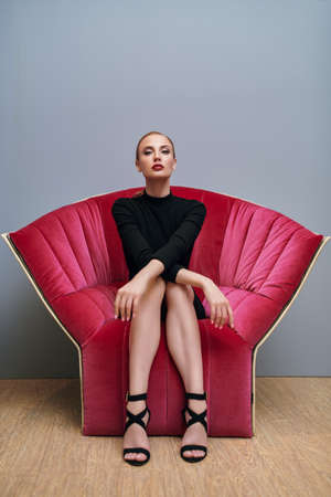 Portrait of a stunning fashionable woman in a black tight dress sitting in a luxurious red armchair. Modern interior, furniture.