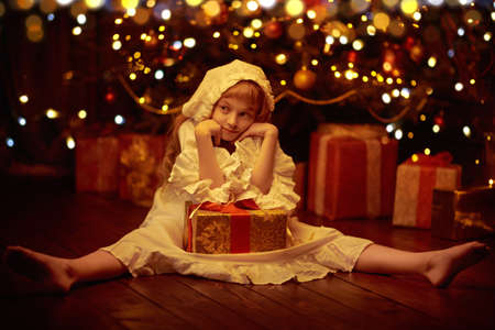 Fairy tales for Christmas. A cute little girl in a nightgown and a cap sits by the Christmas tree with a gift box. There are magic lights around.