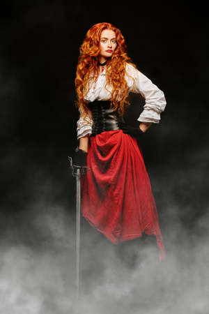 Historical reconstruction of the 16-17th centuries. Full length portrait of a beautiful red-haired woman with a battle epee (rapier). The heroine of an adventure novel.