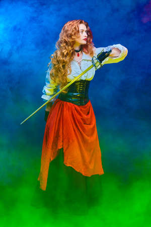 Full length portrait of a beautiful red-haired woman with a battle epee (rapier). Historical reconstruction of the 16-17th centuries. The heroine of an adventure novel. Banque d'images