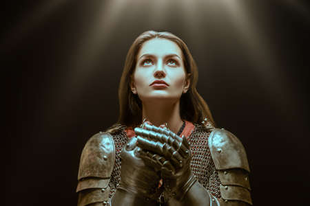 Medieval knight woman in armor prays, blessing before the battle. Reklamní fotografie