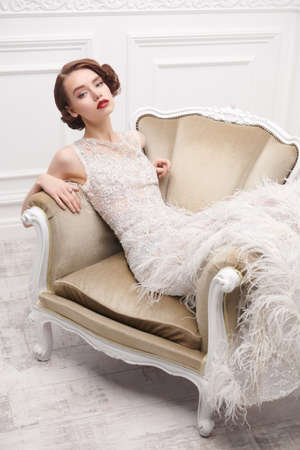 Portrait of a beautiful chic woman posing in a luxury white dress in vintage armchair. Evening makeup and hairstyle of the 20s. Banque d'images