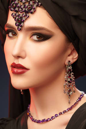 Arabian beauty, fashion. Close-up portrait of a beautiful oriental woman with traditional make-up, black hijab and jewelry on a black background. Make-up and cosmetics.