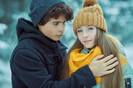 Couple of happy romantic young people teenagers hugging in a winter park and smiling. Winter season.