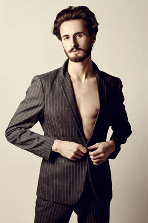 Men's fashion. Handsome brunet man fashion model poses in classic suit and with torso. Studio shot.