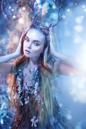Fairytale character. Fabulous forest nymph with horns and blonde hair covered with ice.