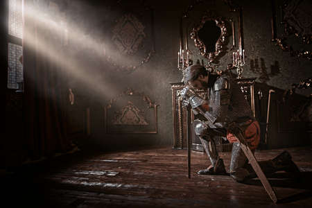 Medieval knight in armor knelt down and reads a prayer in the castle before the battle. Stockfoto