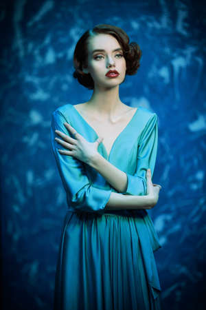 Beautiful melancholic girl in an elegant dress stands against the grunge background. Hair and makeup in the style of the 20s.