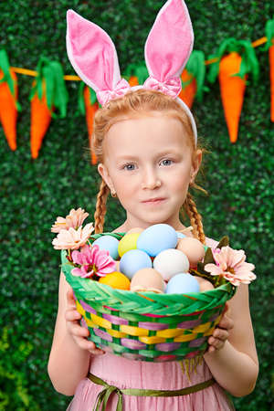 Portrait of redhead little girl with bunny ears holding basket with colorful eggs. Easter holiday. Childhood. Spring-summer season.