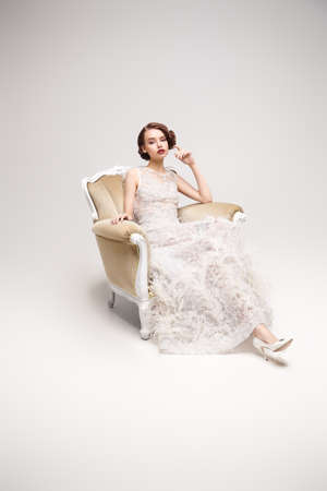 Evening makeup and hairstyle of the 20s. Full length portrait of a beautiful chic woman posing in a luxury white dress in vintage armchair.