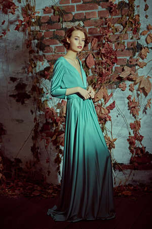 Full length portrait of a beautiful sophisticated girl in an elegant dress standing by the old vintage wall. Hair and makeup in the style of the 20s.