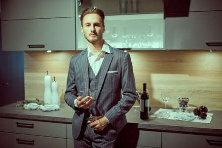 Handsome brunet man in an elegant suit stands with a wine glass in a luxury apartment. Male beauty, fashion.