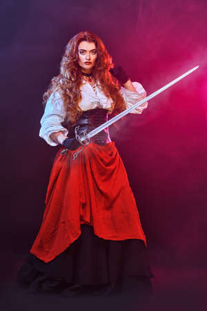 Beautiful redhead woman poses with a battle epee (rapier) on a black background with fuchsia light in the haze. Historical reconstruction of the 16-17th centuries. Banque d'images