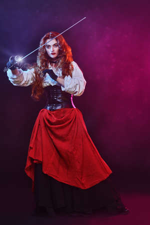 Portrait of a courageous woman with long foxy hair posing with a battle epee (rapier) on a black background with fuchsia light in the haze. Historical reconstruction of the 16-17th centuries. Copy space.