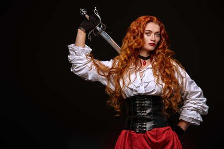 Swordswoman of Middle Ages. Redhead girl poses with a battle rapier on a black background. The heroine of an adventure novel. Copy space.