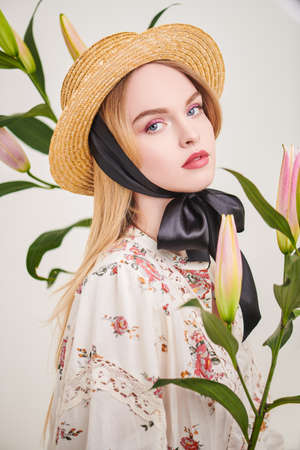 Attractive blonde girl in a straw hat and a summer blouse posing with lily flowers on a white background. Inspiration of spring and summer. Light fresh makeup in pink colors. Perfume and cosmetics.