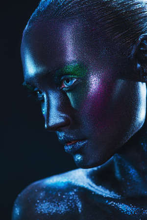 Close-up portrait of a high fashion model woman with black painted skin and sparkling glitter makeup posing in dark with light. Beauty art portrait. Makeup and cosmetics.