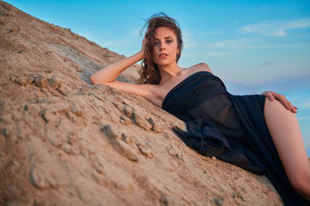 Gorgeous young woman in black swimsuit poses on the sand in the desert at sunset. Fashion shot. Banco de Imagens