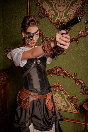 Beautiful confident lady steampunk stands with a gun in a room with vintage victorian interior. World of steampunk.