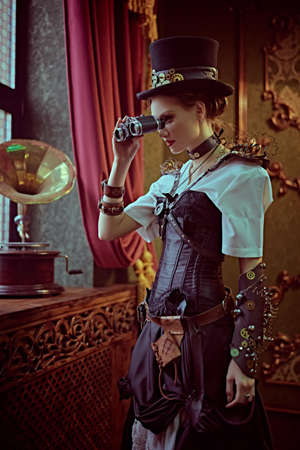 Beautiful confident lady steampunk stands looks through the binoculars at the window in a room with vintage victorian interior. World of steampunk.