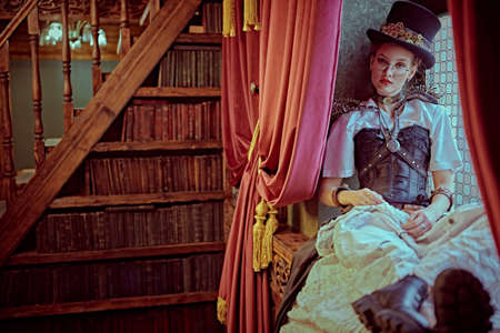 Portrait of a charming steampunk lady sitting on a windowsill in a room of libraries with Victorian vintage interior. 写真素材