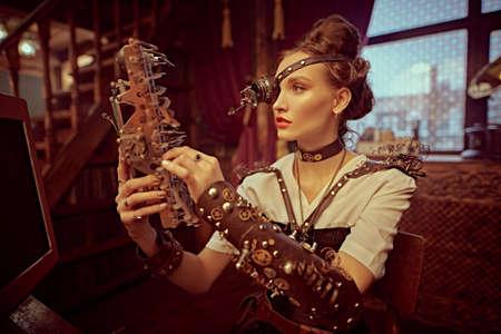 Steampank fantasy world. Beautiful steampunk lady scientist inventor works in her laboratory with Victorian interior.