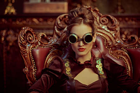 Beautiful steampunk woman with a glasses sits in an armchair in a room with vintage victorian interior. Science fiction, adventures. 写真素材