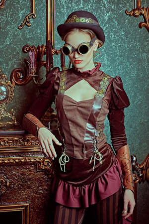 Portrait of a beautiful steampunk lady in futuristic glasses standing in a room with Victorian vintage interior. Steampunk world.