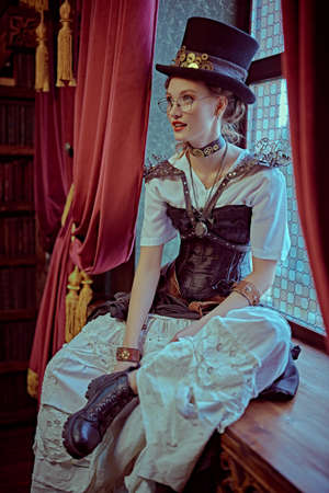 Portrait of a charming steampunk lady sitting on a windowsill in a room with Victorian vintage interior.