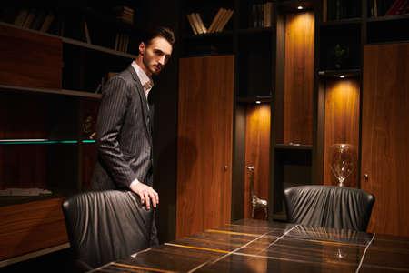 Handsome brunet man in an elegant suit man stands in a luxury office. Mafia. Male beauty, fashion.