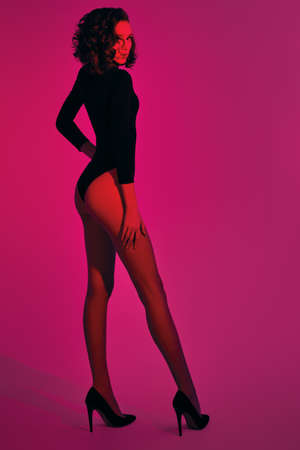 Full length portrait of a beautiful slender woman alluring in black bodysuit and high-heeled shoes in color mixed light. Fashion studio shot. Make-up and hairstyle.
