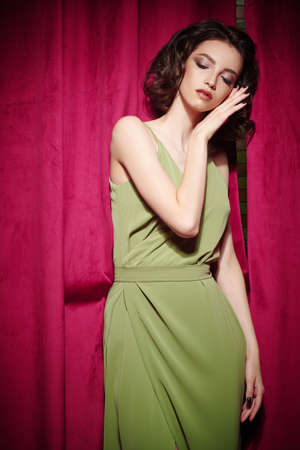 Dreamy brunette girl with evening make-up and hairstyle with closed eyes posing in elegant dress against the background of burgundy velvet curtains. Fashion shot. 写真素材