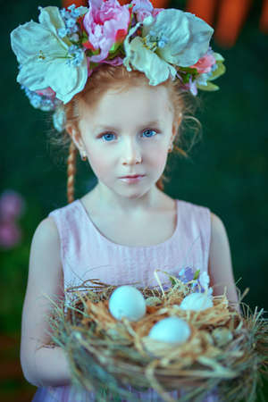 Portrait of redhead little girl with with a flower wreath holding nest with light eggs. Easter holiday. Childhood. Spring-summer season.