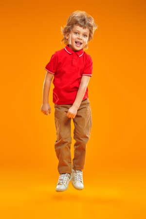 Full length portrait joyful boy in bright summer clothes bouncing on a yellow background at studio. Summer children's fashion. Reklamní fotografie
