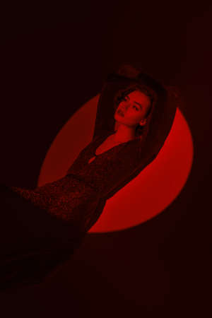 Art portrait of stunning young woman in a long elegant dress and with hair and makeup in the style of the 20s posing in the circle of red light. Light and shade. 写真素材