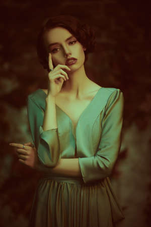 Beautiful pensive girl in an elegant dress stands against the background of an old vintage wall. Art fashion. Hair and makeup in the style of the 20s. 写真素材