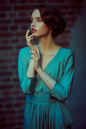 Sensual beautiful girl in an elegant dress stands against the grunge background. Hair and makeup in the style of the 20s.