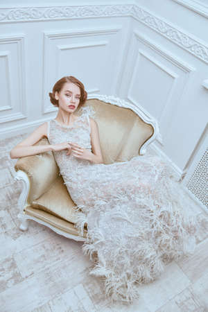 Portrait of a beautiful chic woman posing in a luxury white dress in vintage armchair. Evening makeup and hairstyle of the 20s. 写真素材