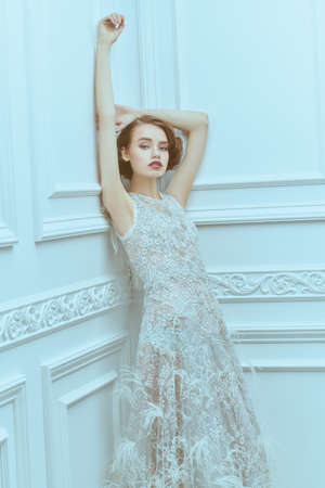 Sensual young woman in a white luxury dress poses in a white room with classic vintage interior. Fashion shot. Wedding dress.